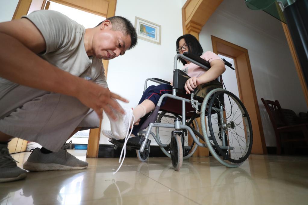 去学校报到的当天早上,谢培军帮女儿穿鞋。(曹正平摄)