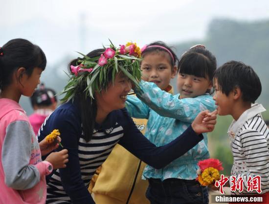 资料图:孩子们亲手编花环祝贺老师节日快乐。中新社记者 翟羽佳 摄